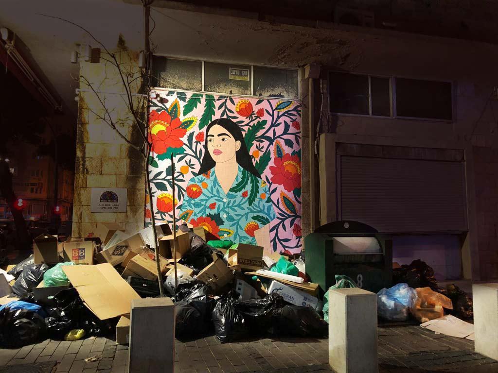 האשה בציור הקיר צופה על הרי הזבל בעיר התחתית - שביתת עיריית חיפה (צילום: ליאת מולכו)