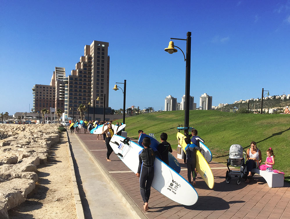 """חוף הים הוא לא נדל""""ן - גולשי גלים בטיילת החוף הדרומי. ברקע - מלון מרידיאן - מגדלי חוף הכרמל (צילום: ירון כרמי)"""