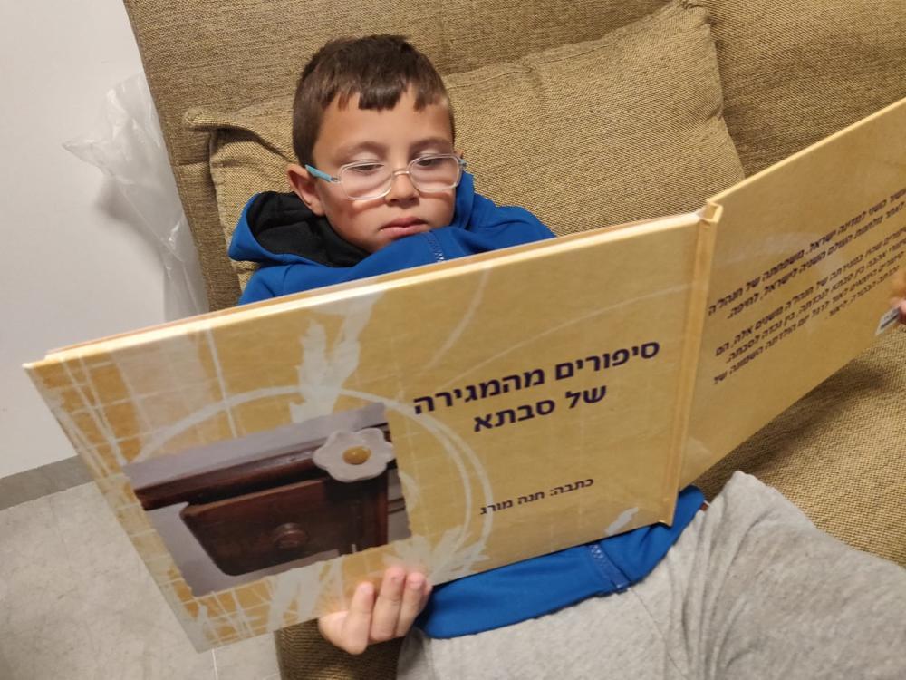 נכדה של חנה מורג. קורא את ספרה של סבתא. (צילום: אלבום אישי).