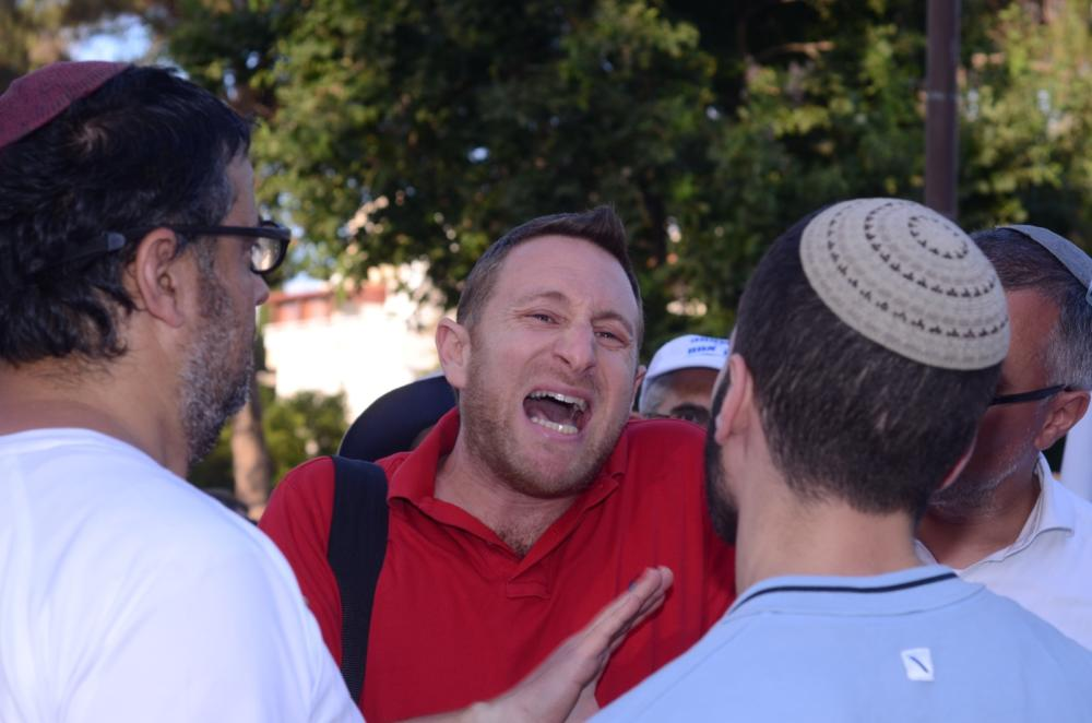 מפגין מול מאות מפגינים בצעדת המשפחה בנווה שאנן בחיפה 27/6/2019 (צילום: מיכל ירון)