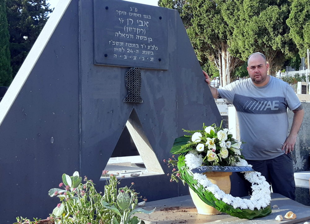 """לירן (אלזסר) חולצה אפורה ליד מצבתו של אבי רן ז""""ל, בבית העלמין בחיפה (צילום: אדיר יזירף)"""