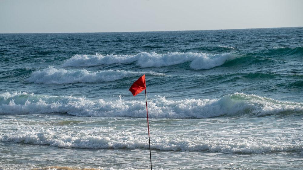 דגל אדום מונף בחוף הים של חיפה בשקיעה (צילום: ירון כרמי)