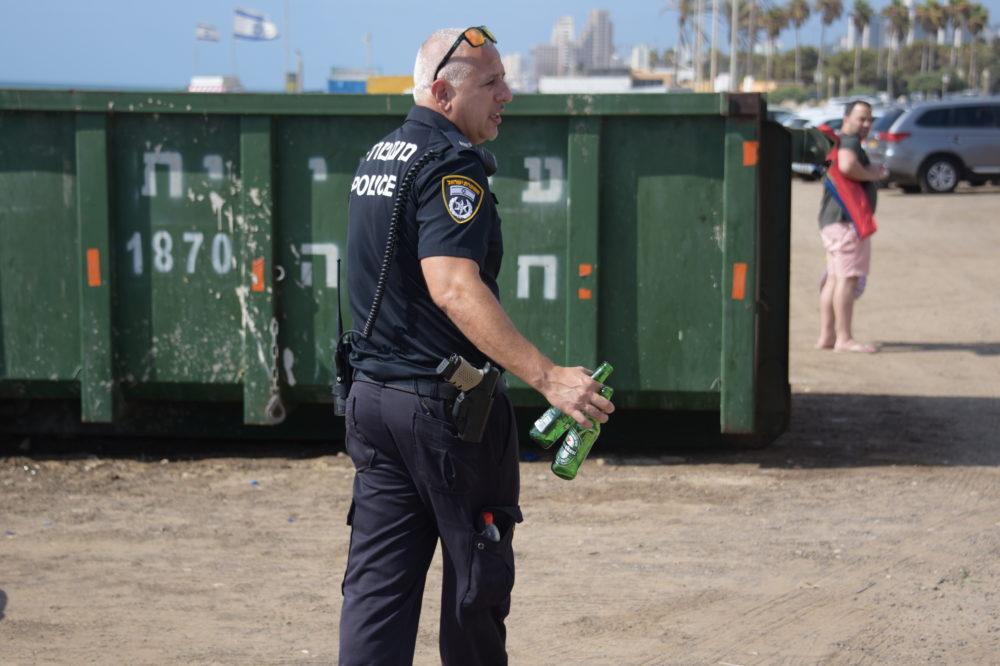 שוטר עם בקבוקים מזכוכית חוף הים בחיפה( קרדיט דוברות המשטרה)