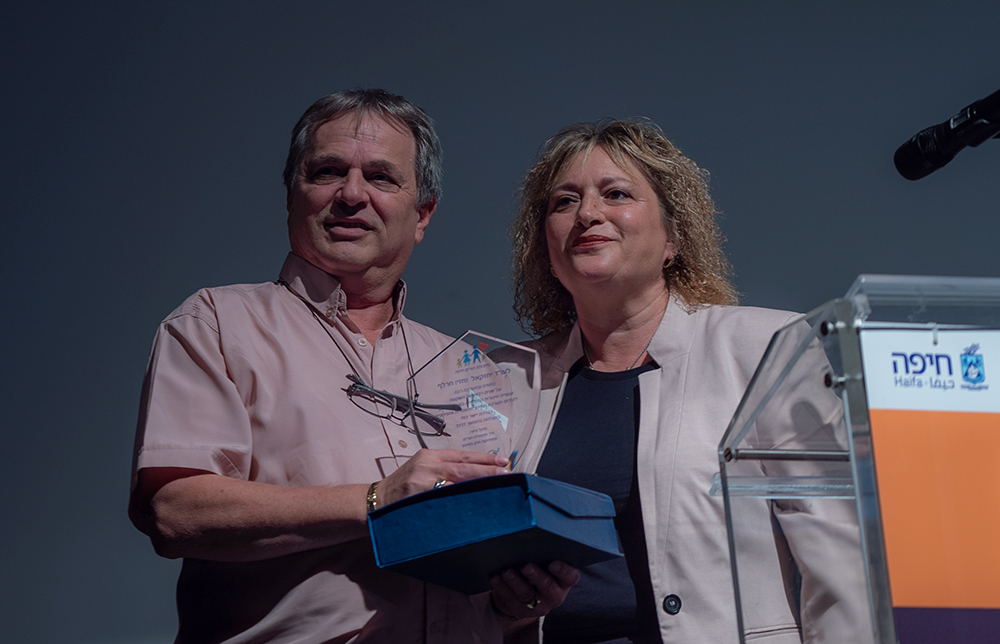"""סיגל ציוני מעניקה מגן הוקרה לחזי חרל""""פ על תרומתו לוועד ההורים הישובי (צילום: ירון כרמי)"""
