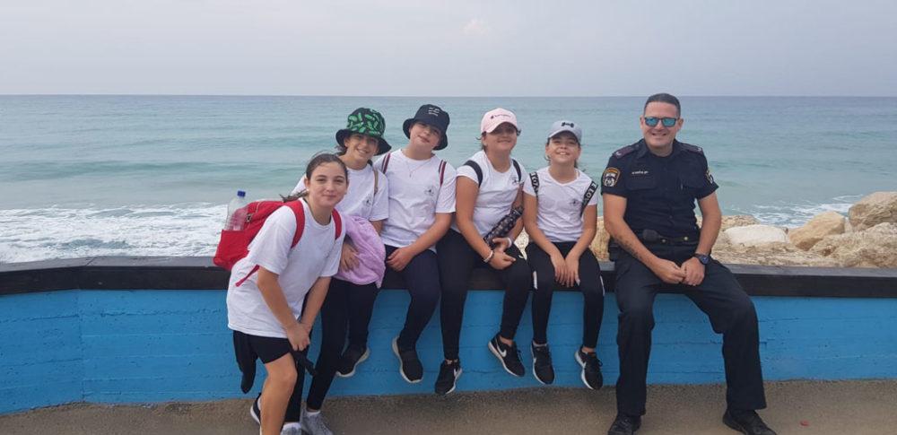 ילדי בית הספר אהוד עם שוטר המאבטח את יום ההליכה הבינלאומי בטיילת חוף הים בחיפה (צילום: מאיה שפירר-אבני)