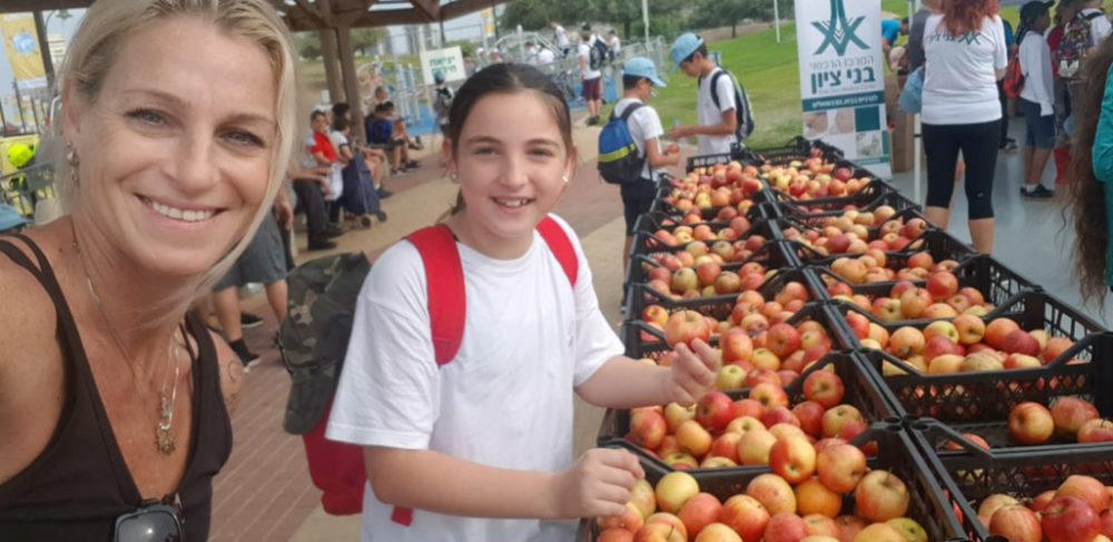 מאי שפירר וביתה לייד דוכן מלא בתפוחים • יום ההליכה הבינלאומי בטיילת חוף הים בחיפה (צילום: מאיה שפירר-אבני)