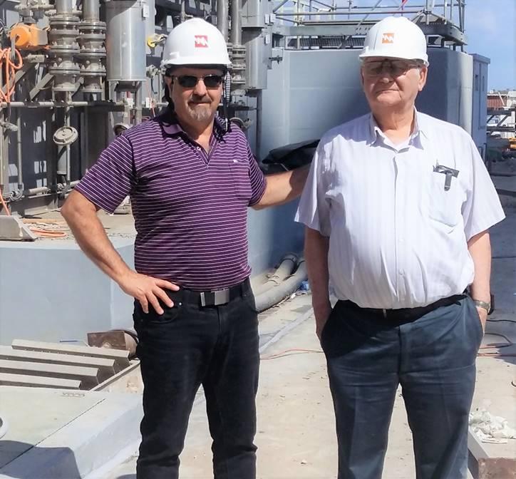 """ד""""ר דן יצחקי ז""""ל עם ירון חנן בסיור בתחנת הכח של חברת החשמל בחדרה, בצילום ליד מתקן האוריאה (ספט' 2016)"""