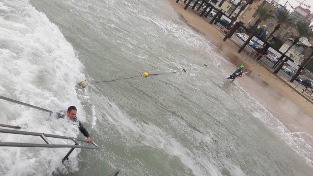 גולש הרוח בחוף מבטחים והמציל (משמאל) עולה בחזרה לחוף (צילום: חי פה)