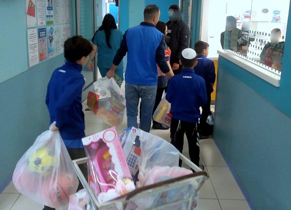 """ילדי הקבוצה מחלקים מתנות במחלקות ביה""""ח """"רות"""" לילדים ברמב""""ם (צילום: דוברות מועדון הכדורגל """"מכבי נווה שאנן אלדד"""")."""