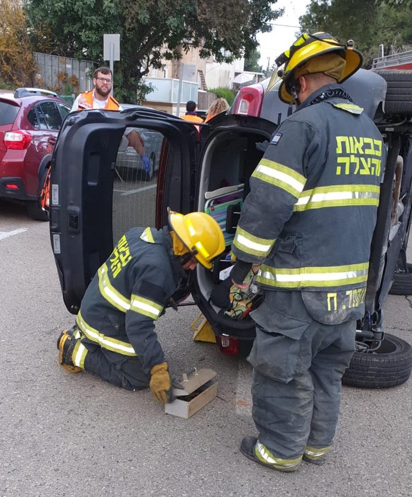רכב הקיה התהפך בתאונה עצמית ברחוב בורוכוב בחיפה הנהג חולץ מהדלת האחורית (צילום: לוחמי האש)