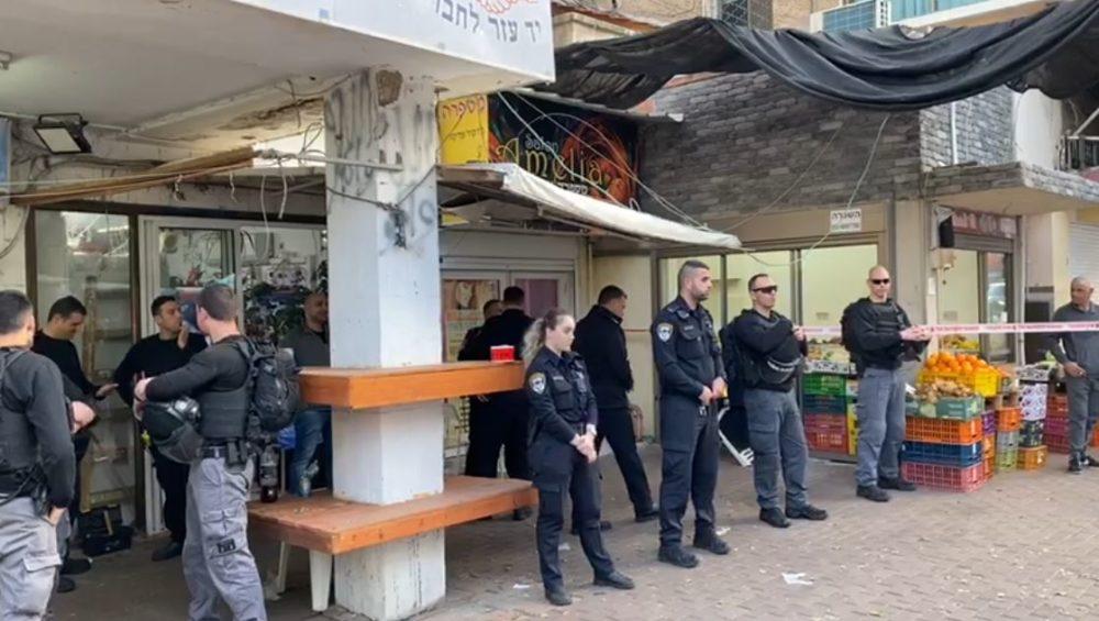 שוטרים בפתח חנותו של שאדי בנא - המחבל שירה הבוקר בירושלים (צילום: שמעון סבג)