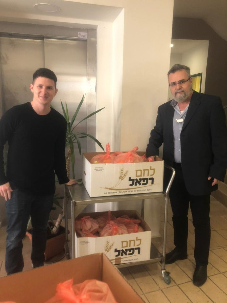 הרב דב חיון סגן ראש העיר חיפה  עם עוזרו ארנון בחלקת מזון לקשישים (צילום: מירב אסידו)