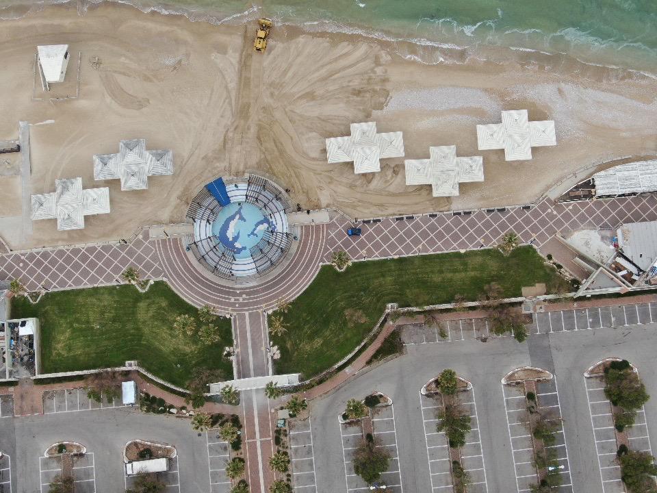 דחפור מסדר את החול מול בריכת הדולפין • העיר חיפה ריקה בתקופת סגר הקורונה (צילום רחפן: מרום בן-אריה)