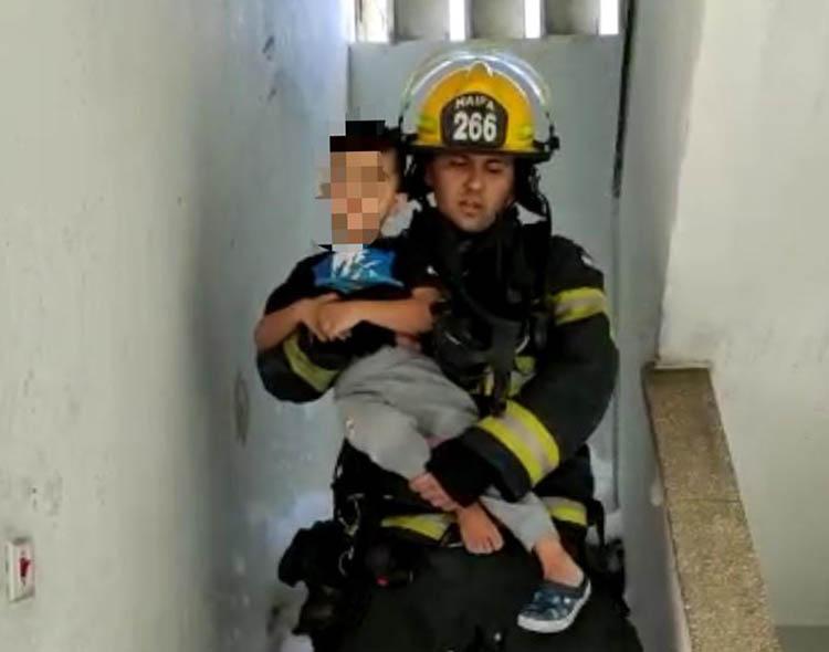 """כבאי מחלץ ילד בשרפה בבית מגורים ברחוב ש""""י עגנון בחיפה (צילום: לוחמי האש)"""