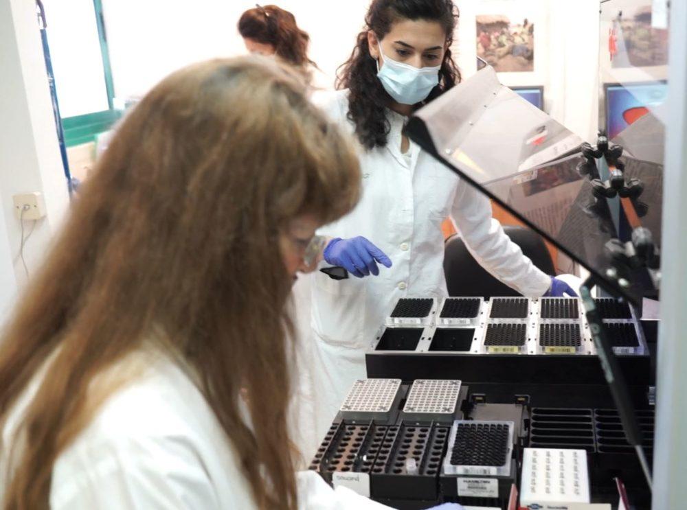 """ד""""ר אלסה פבלוצקי מזינה רובוט המבצע בדיקות קורונה • מסע מצולם במעבדת כללית בנשר (צילום: ירון כרמי)"""