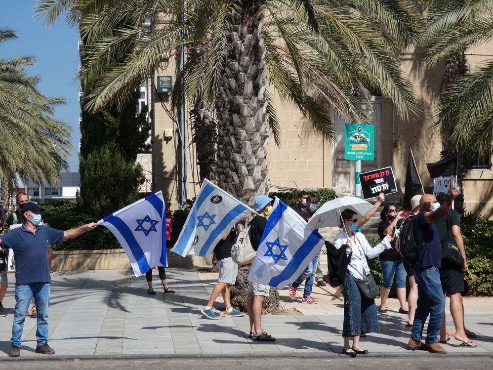 """דגלי ישראל בהפגנה - הפגנת הדגלים השחורים ברחבת בית החולים רמב""""ם בחיפה בעת ביקור נתניהו (צילום: חי פה בשטח)"""