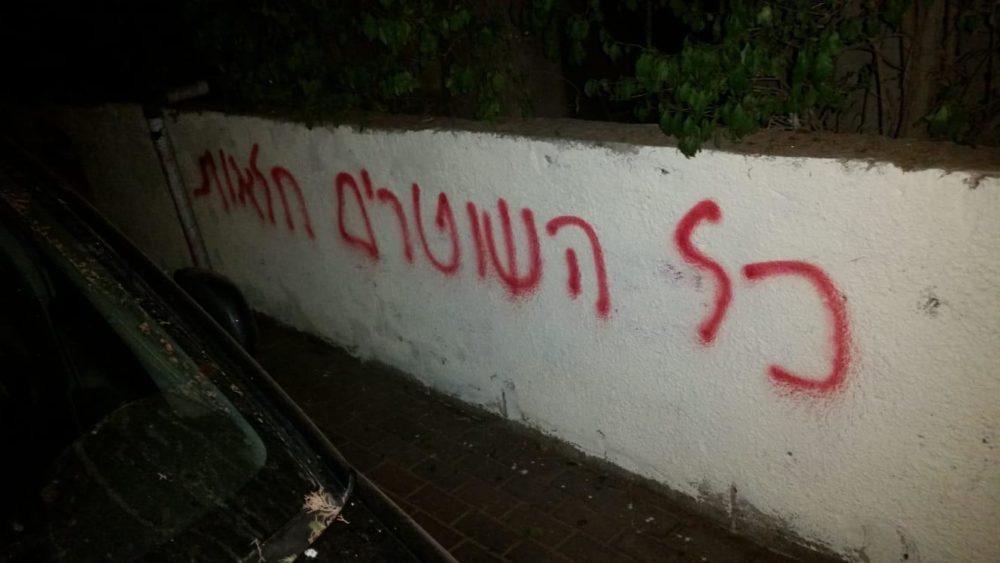 כתובות נאצה בגנות משטרת ישראל על קירות ברחוב מסדה בהדר הכרמל בחיפה (צילום: חי פה)