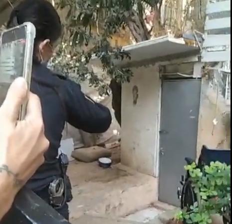 שוטרים בפתח בית, בו היה חשד להתעללות בכלב (צילום: פעילים מהשטח)
