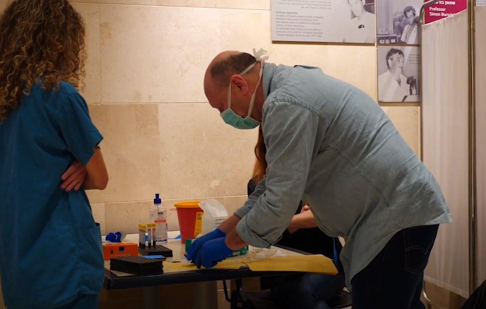 """מבצע בדיקות סרולוגיות לקראת חיסוני קורונה (צילום מסך: הקריה הרפואית רמב""""ם)"""