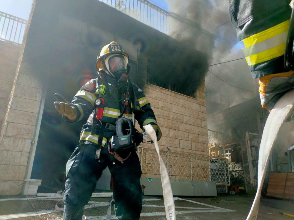 כבאי בפעולה • שרפה ברחוב קיבוץ גלויות בחיפה | חנות חומרי חשמל נשרפה כליל (צילום: כבאות והצלה חיפה)