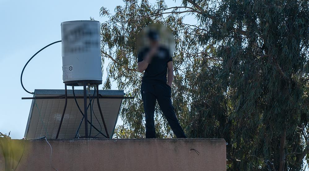 חיפה - רחוב אדמונד פלג - אדם מתבצר על הגג, זורק אבנים ומאיים להתאבד (צילום: חי פה)