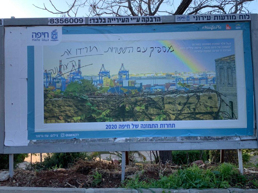 """שלט חוצות של העירייה - תחרות התמונה של חיפה • מישהו כתב: """"מספיק עם שטויות, תורידו את הארנונה!"""" (צילום: חי פה בשטח)"""