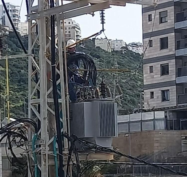 עובד חברת החשמל מתקן את התקלה בשנאי בנווה דוד (צילום: אברהם סעיד)