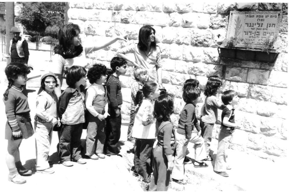 הגננות מסבירות לילדי הגן בתל חנן על לוח ההנצחה ביום הזיכרון 1979 (צילום: שלום שטרסברג)