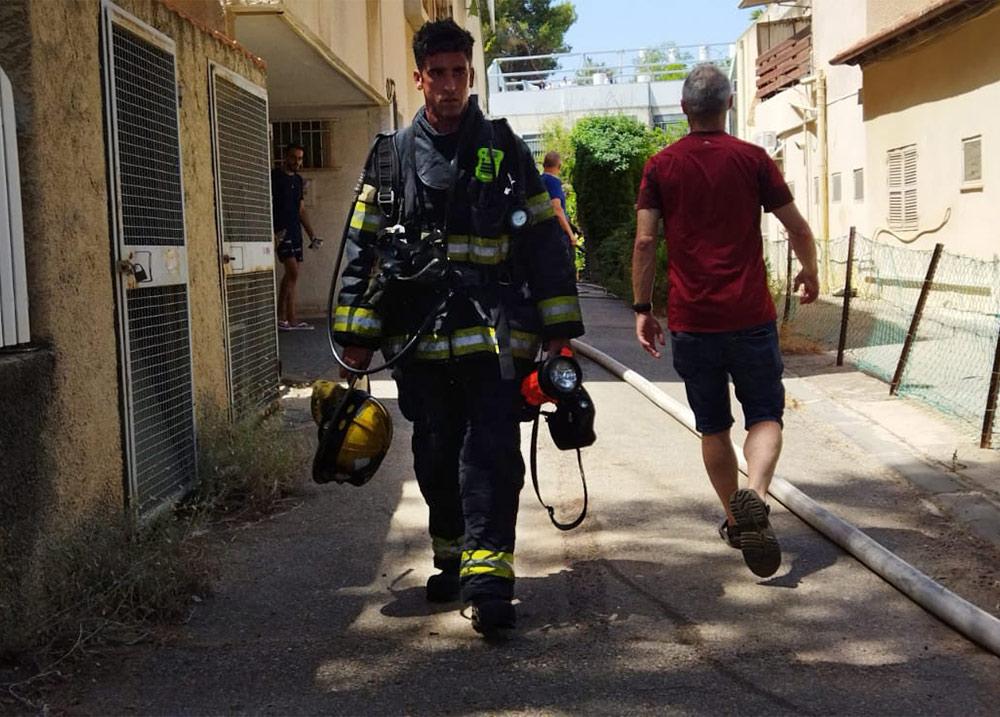 כבאי בשריפה במבנה מגורים ברחוב הגליל בשכונת נווה שאנן בחיפה (צילום: חגית אברהם)