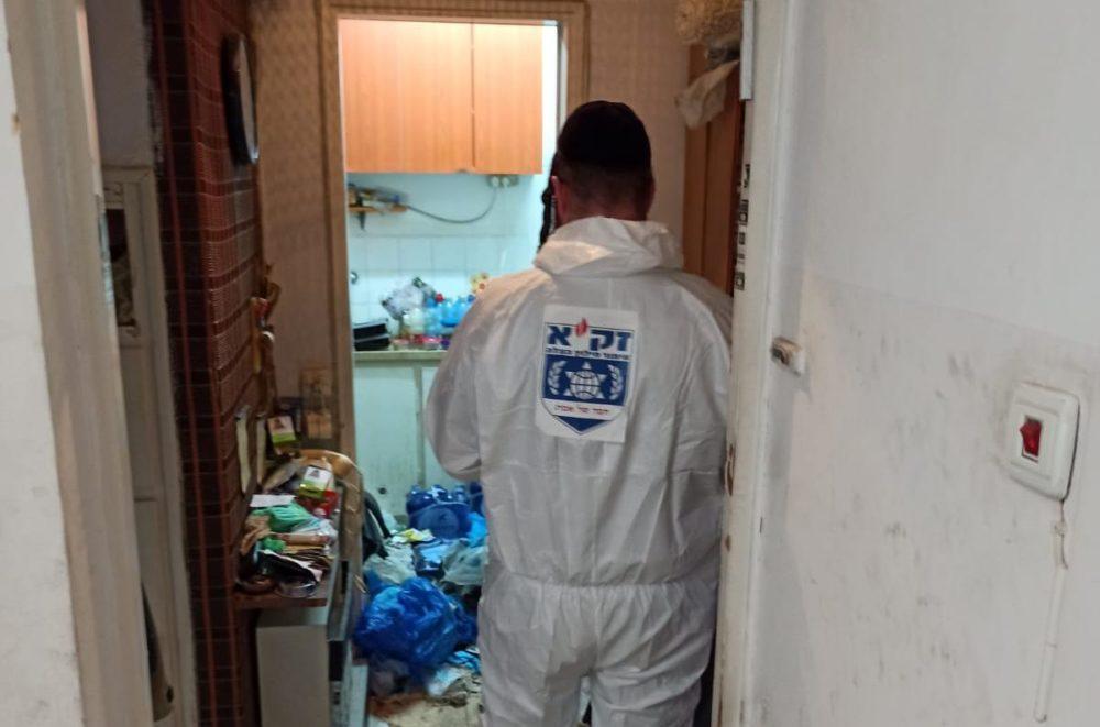 """פינוי גופה שנמצאה במצב ריקבון ברחוב אבא הילל סילבר, בשכונת נווה שאנו בחיפה (צילום: דוברות זק""""א)"""