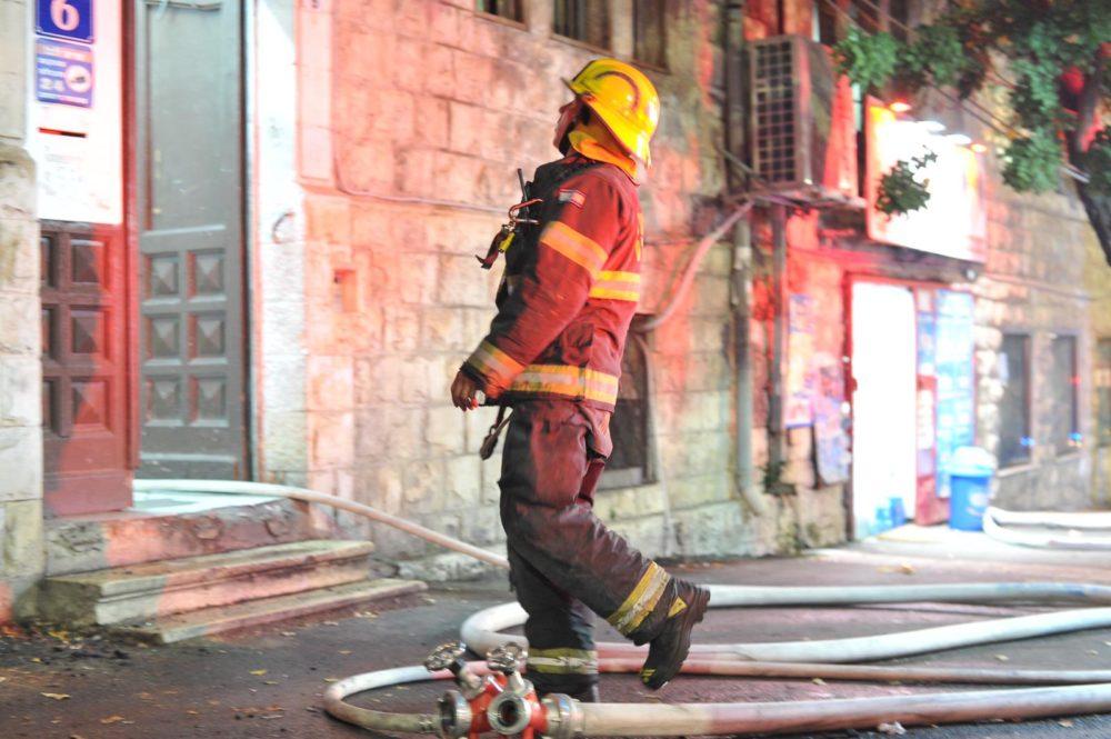 כבאי בשריפה במבנה בן שתי קומות המשמש כפנימייה של ילדים ברחוב ארלוזורוב בהדר שבחיפה (צילום: כבאות והצלה)